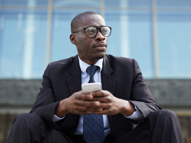 Low angle portrait of contemporary African-American businessman using smartphone sitting on steps outside office building during break and looking away pensively, copy space