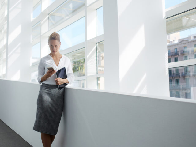 Elegant woman using mobile phone after work on digital tablet while standing in office interior,female manager read text message on cell telephone while waiting for her colleague after finish work day